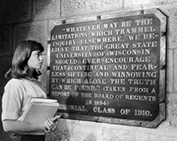 a girl looking at the sift and winnow plaque at bascom hall.