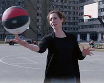 Laura spinning a basketball on her finger.