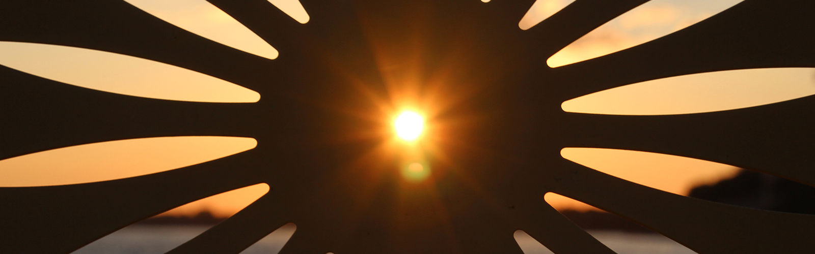 the sunrise shines through the center hole of a memorial union chair.