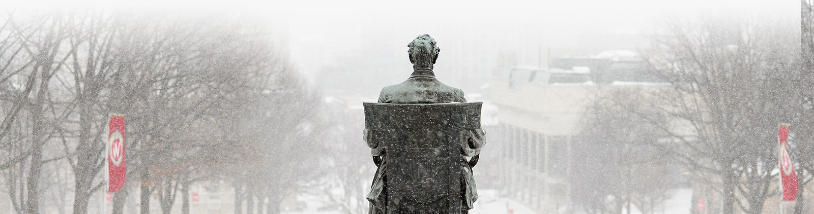 snow falling on a closeup of Abe at bascom hill.